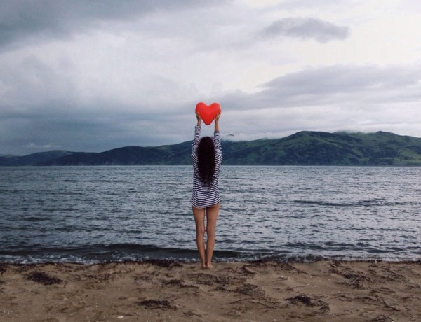 A woman on the beach with a heart signifying that she found love while online dating.