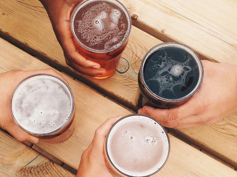 Couples hands with beers on a table while they're on a double date.