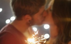 A couple kissing while holding sparklers.