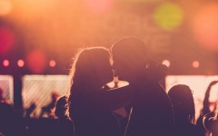A couple in a healthy relationship kissing at a concert after going on a great date night.