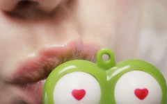 A girl kissing a plastic frog.