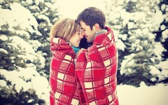A couple in the snow wrapped up in a blanket together snuggling.