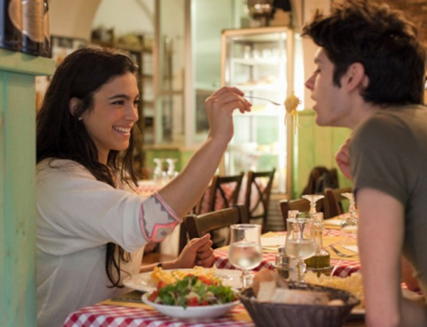 A couple laughing and eating dinner together on their first date.