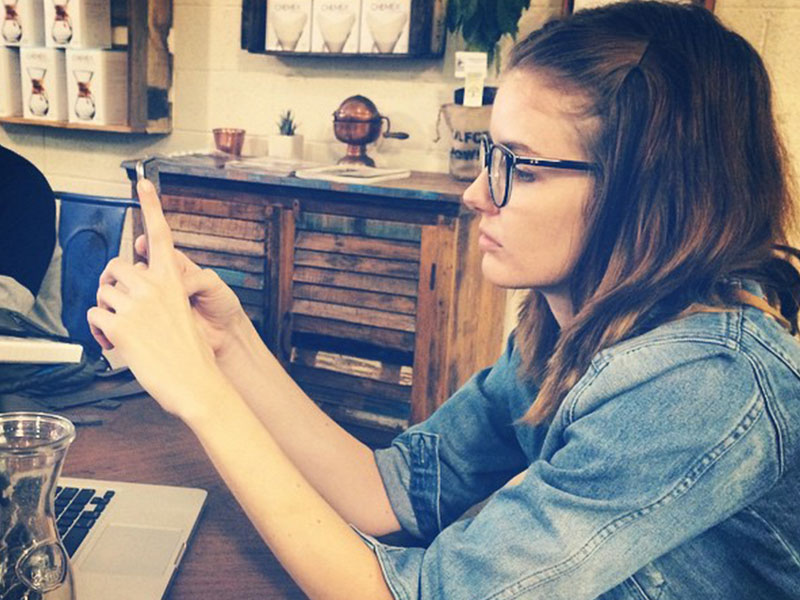 A girl having relationship problems at a coffee shop going through her boyfriend's text messages.