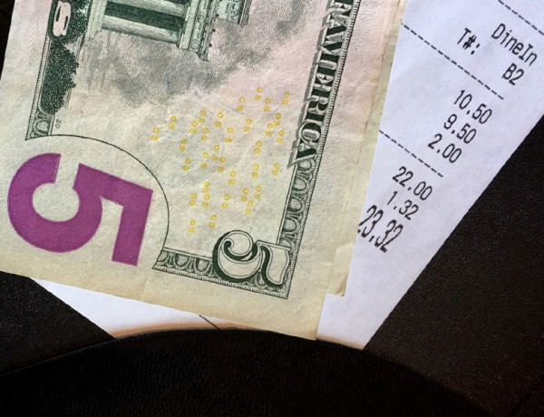 A tip on a table with a receipt.