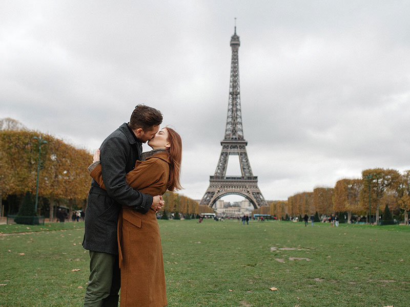 A couple in a healthy relationship kissing in front of the Eiffel Tower.