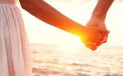 A couple holding hands on the beach.