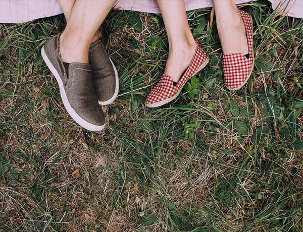 A couple's feet as they lay down on a picnic blanket on a first date.