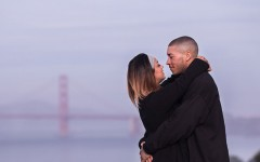 A couple about to kiss in front of the Golden Gate Bridge.