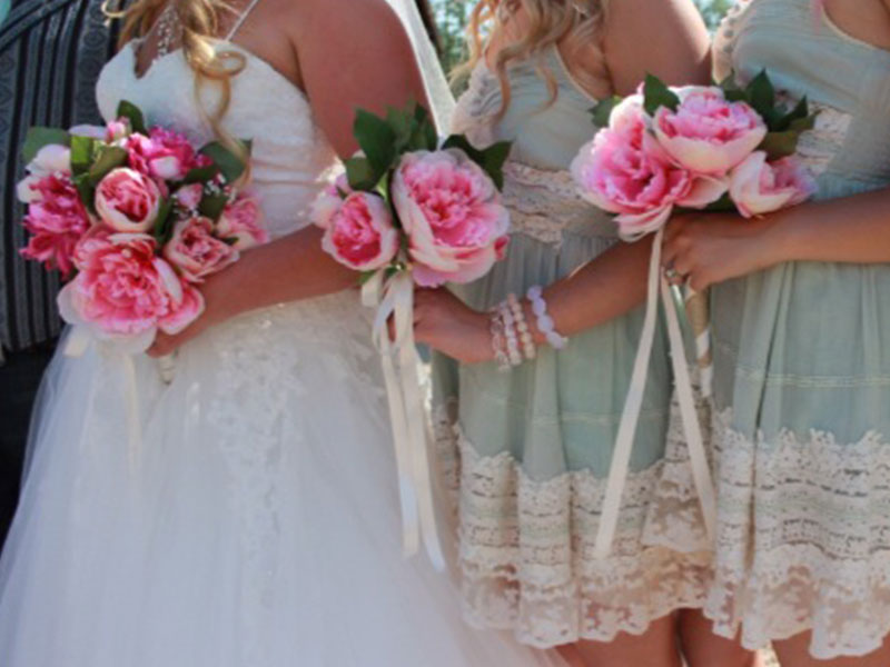 Bridesmaids lined up next to a bride at a wedding.
