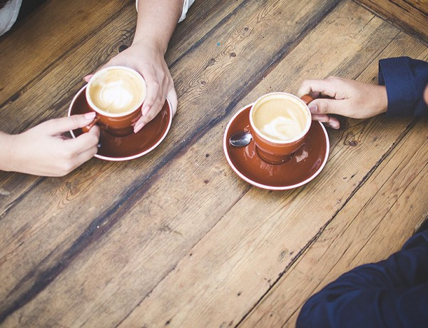 A couple's hands holding coffee cups while they are having a break up conversation.