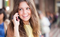 A woman in a healthy relationship smiling and talking on the phone.