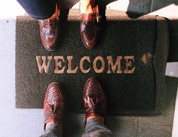 A couple with their feet on the welcome mat, ready to move in together.