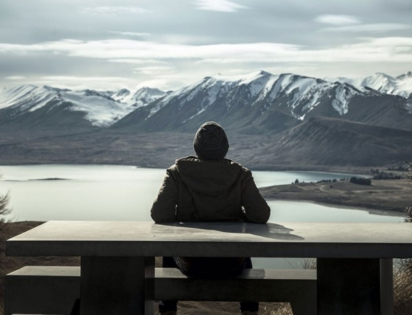 A man having relationship problems sitting alone in front of a mountain to get some me time.