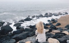 A woman having relationship problems and dealing with long distance at the beach thinking.