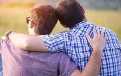 A gay male couple in a meadow hugging.