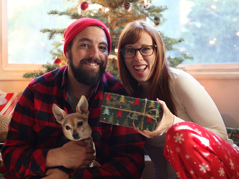 A couple in a healthy relationship in front of a Christmas tree laughing with a dog.
