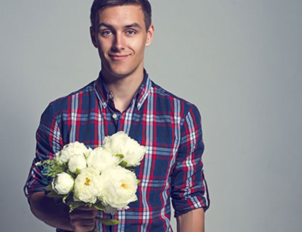 A guy smiling and holding flowers for a date.
