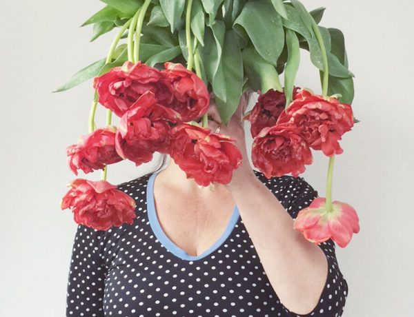A single woman who's alone on Valentines Day holding sad looking flowers in front of her face.