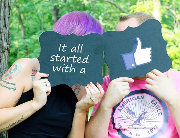 Two people at a wedding holding up signs saying it all started when they friended on Facebook.