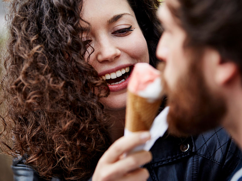 A woman flirting with her date using an ice cream cone.