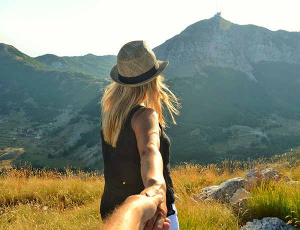 A women running through a spring meadow holding the hand of the man she's dating.
