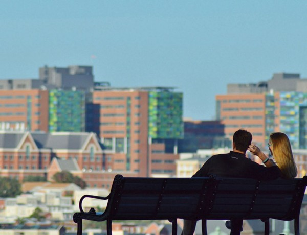 A woman and a man in their 30s on a park bench looking at a city on a date.