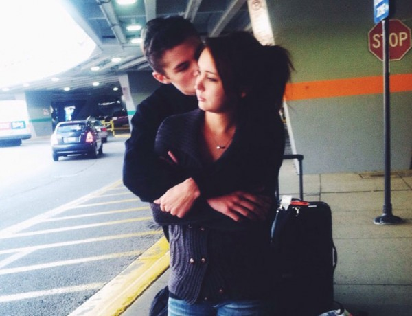 A couple in a long-distance relationship hugging each other at the airport after not seeing each other for a while.