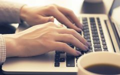 A woman with purple nail polish starting a conversation online while typing on her laptop.