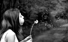 A woman making a wish on a dandelion.