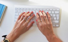 A woman with pink nail polish writing dating profile headlines for her online dating profile.