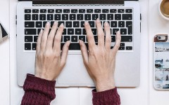 A woman typing on her computer who is online dating and trying to avoid online dating scams.