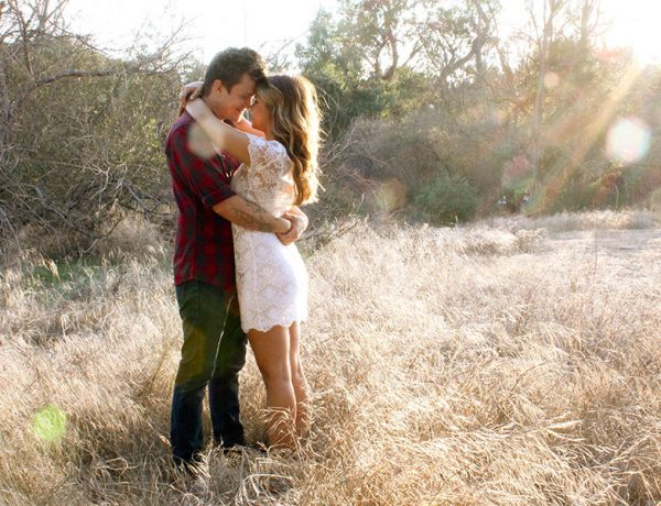 A couple hugging in a field.