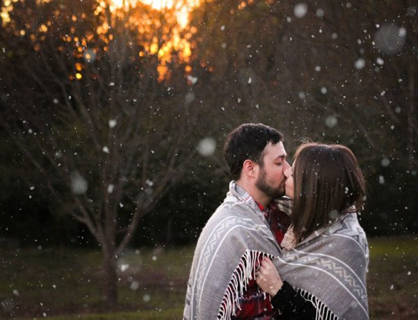 A couple in a healthy relationship who set good relationship goals kissing in the dimming light.
