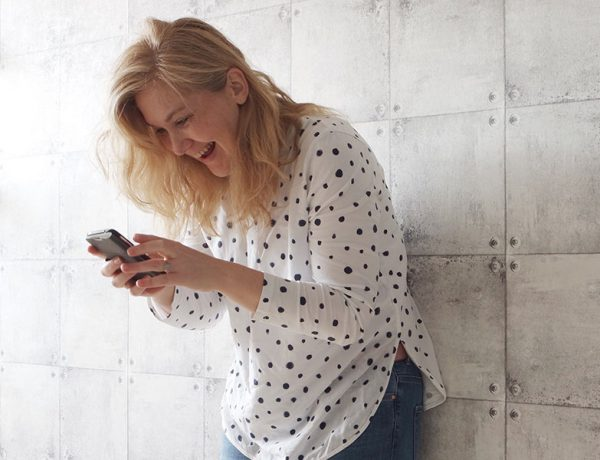 A woman sending flirty texts and laughing.