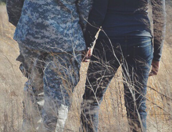 A couple in the armed forces holding hands in a field.