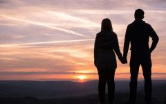 A couple having relationship issues holding hands and looking at the sunset together.
