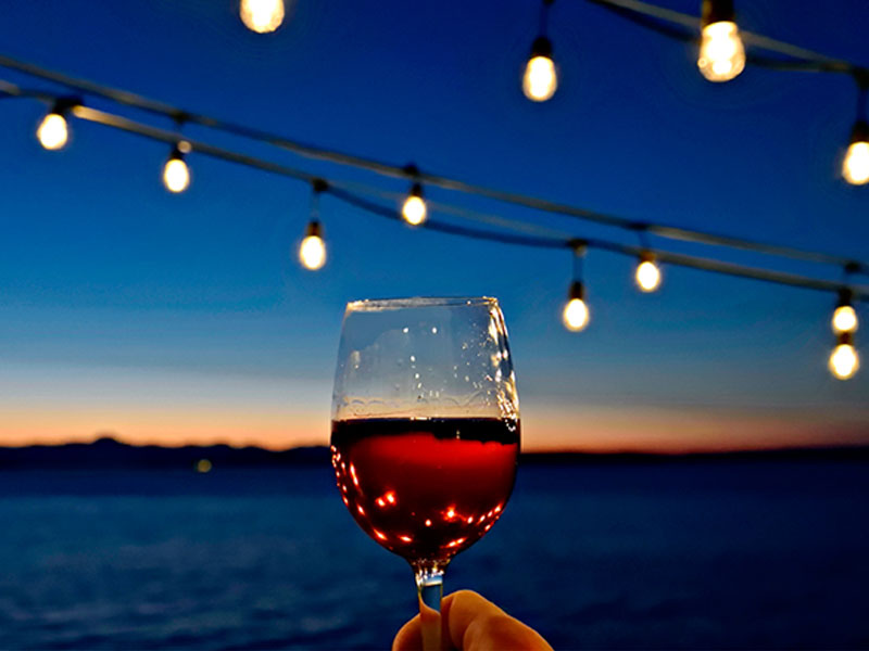 Someone lifting their red wine glass to cheers the sunset in celebration of National Wine Day.