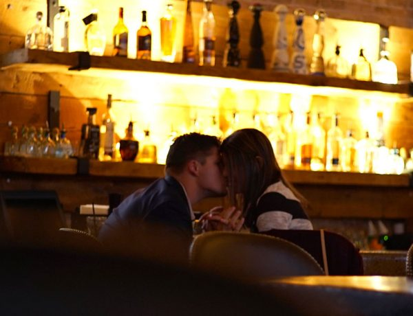Two people kissing while sitting at the bar.