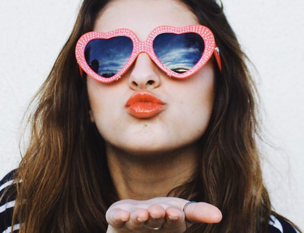 A girl who's dating multiple people blowing a kiss.