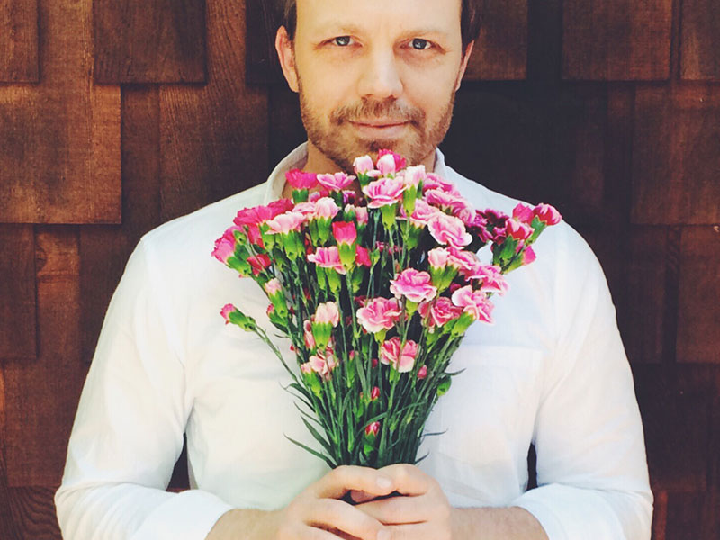 A man in his 40s holding flowers for a date with a woman.
