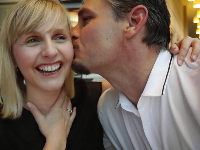 A women in her 40s laughing as a man kisses her cheek on a date.