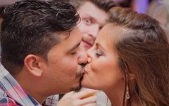 A single guy living the single life watching a happy couple kiss.