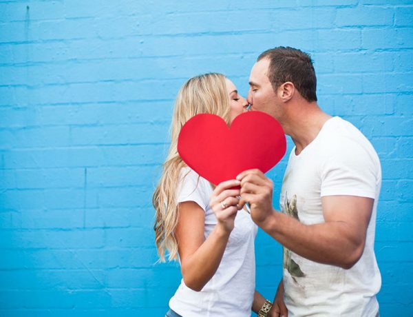 A couple following a new relationship timeline kissing and holding a heart.