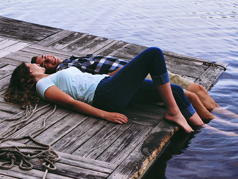A couple having the relationship talk while laying on a dock with their feet in the water.