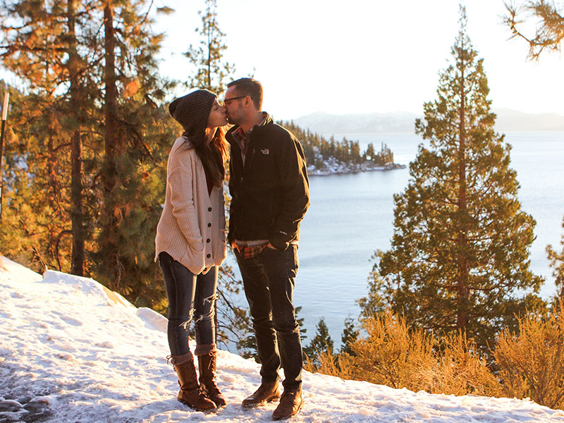 The man kissing a woman in front of a lake took some good relationship advice for men to make her happy.