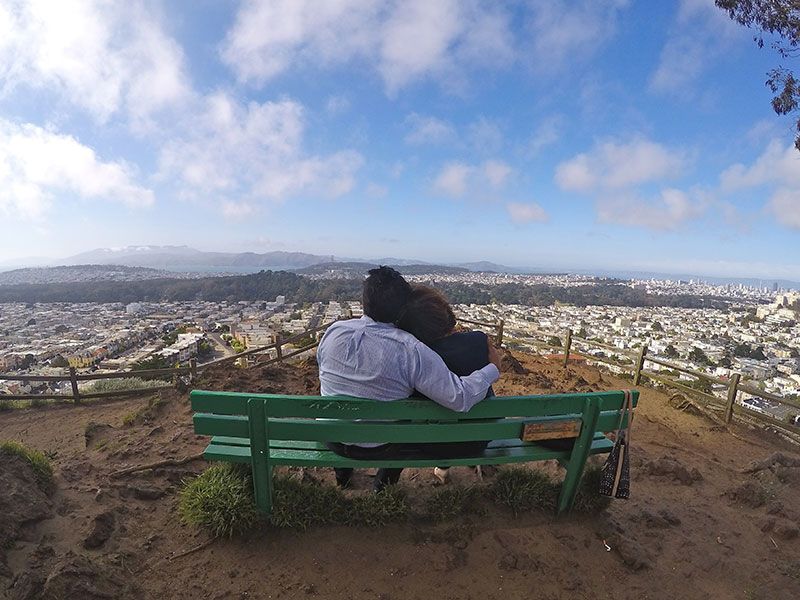 A couple dating after 50 sitting on a bench looking over a city.