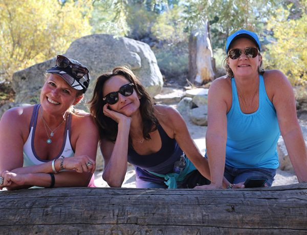 A group of happy women over 50 smiling while taking a break on a hike.