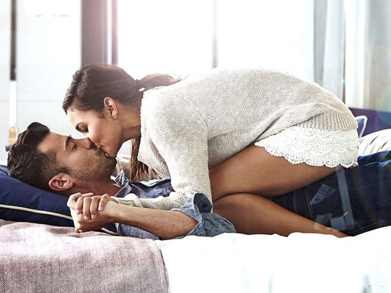 This couple kissing on a bed are the definition of an exclusive relationship.