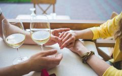 A couple's hands touching across a dinner table where they're dating after divorce.